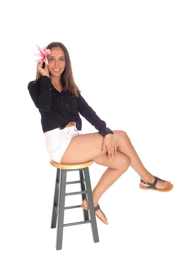 Mulher bonita que senta-se no short na cadeira imagens de stock