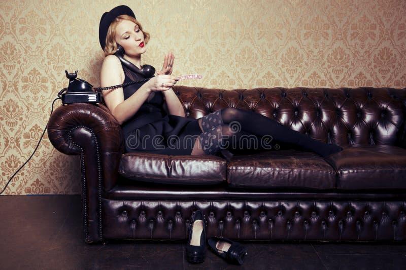 Mulher bonita que senta-se no sofá foto de stock