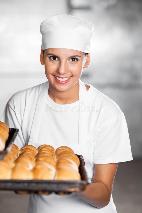 Mulher bonita que sorri ao guardar o pão Tray In Bakery fotografia de stock