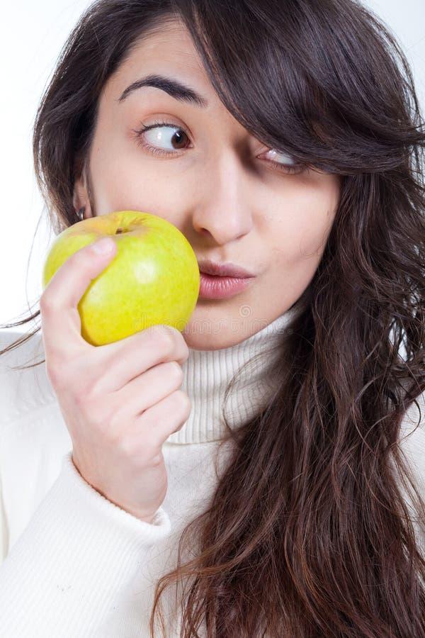 mulher bonita que sorri com uma maçã verde disponível foto de stock