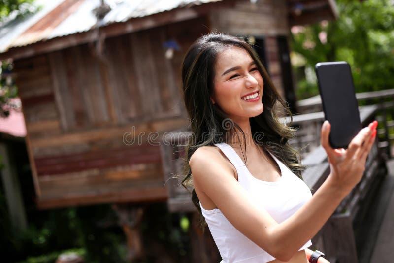 Mulher bonita que sorri e que faz o selfie por seu telefone esperto imagem de stock