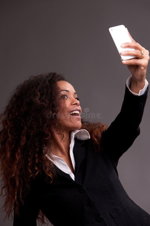 Mulher bonita que sorri em seu telefone foto de stock