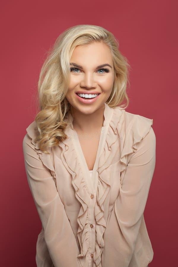 Mulher bonita que sorri, levantando e olhando a câmera no fundo cor-de-rosa colorido Menina loura com penteado encaracolado louro foto de stock