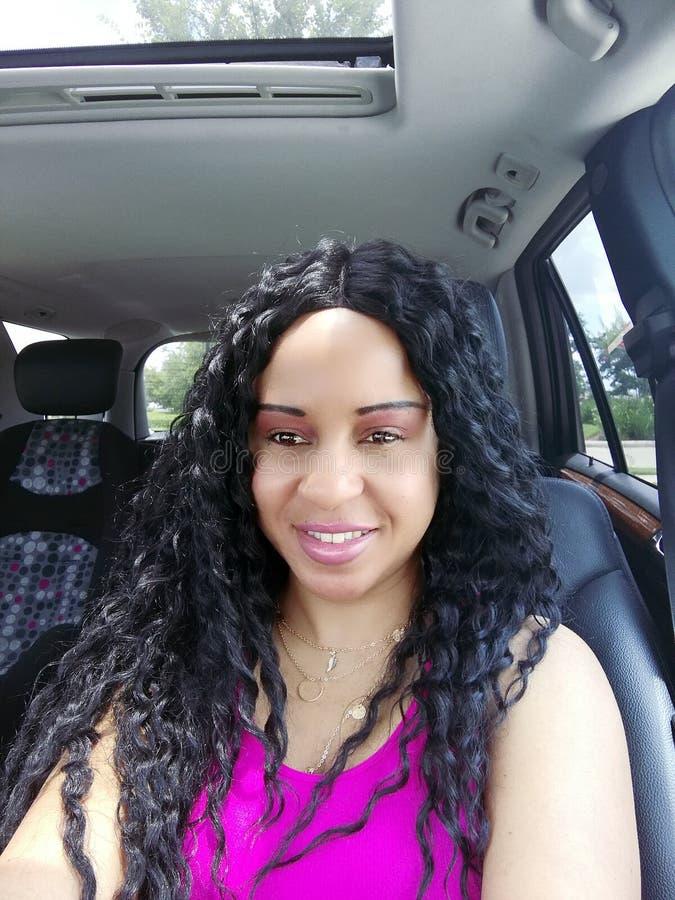 Mulher bonita que sorri no retrato do carro com criança Seat na parte traseira fotografia de stock