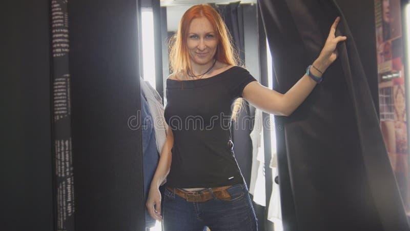 Mulher bonita que tenta no revestimento das calças de brim em sala apropriada da loja imagens de stock royalty free
