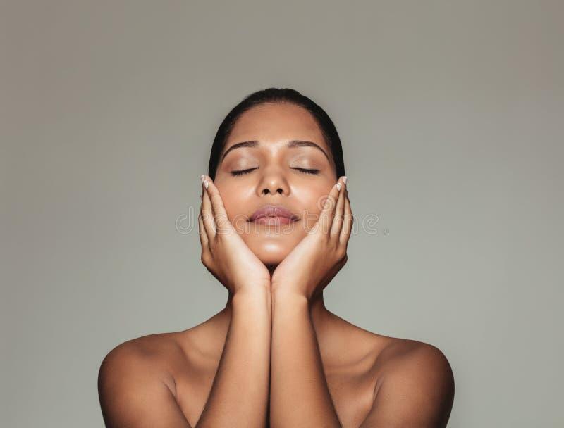 Mulher bonita que toca em sua cara limpa fresca fotografia de stock