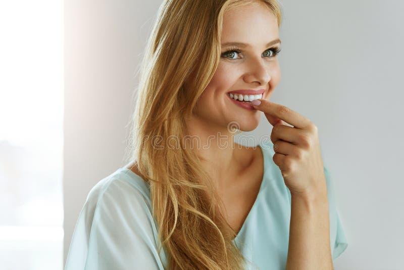 Mulher bonita que toma o comprimido, medicina Vitaminas e suplementos foto de stock