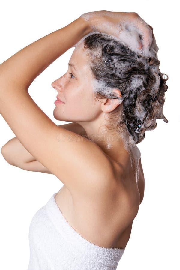 Mulher bonita que toma um chuveiro e que shampooing seu cabelo cabelo de lavagem com champô imagem de stock
