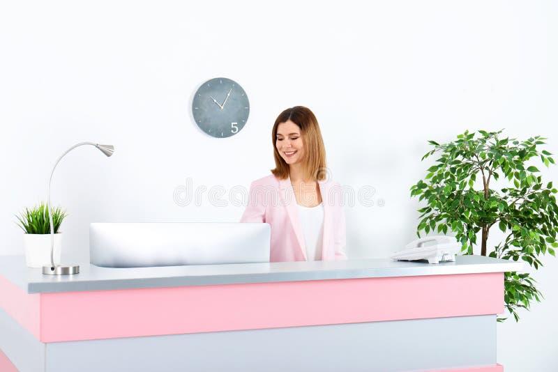 Mulher bonita que trabalha na mesa de recep??o imagem de stock