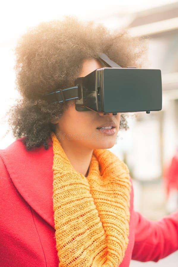 Mulher bonita que usa a elevação - vidros da realidade virtual da tecnologia exteriores imagens de stock