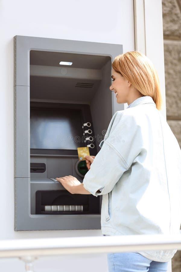 Mulher bonita que usa a máquina de dinheiro para a retirada do dinheiro fotografia de stock royalty free