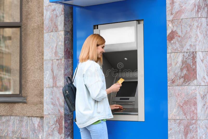 Mulher bonita que usa a máquina de dinheiro para a retirada do dinheiro imagens de stock royalty free