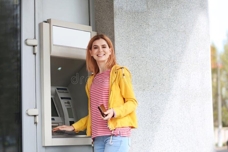Mulher bonita que usa a máquina de dinheiro para a retirada do dinheiro fora imagens de stock