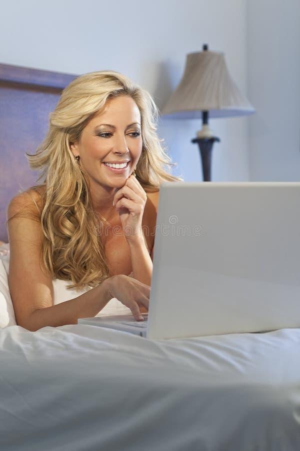 Mulher bonita que usa o computador portátil na cama foto de stock royalty free