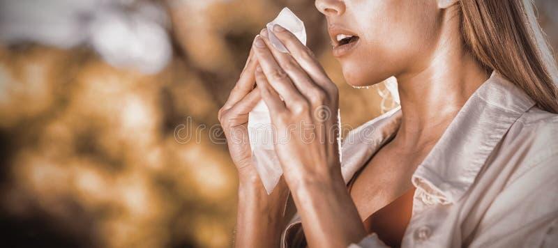 Mulher bonita que usa o tecido ao espirrar fotografia de stock