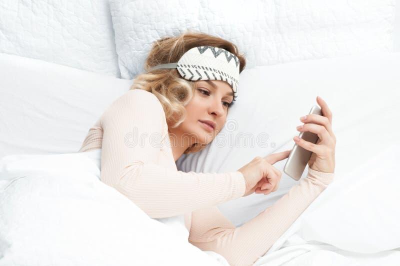 Mulher bonita que usa seu telefone celular na cama fotos de stock