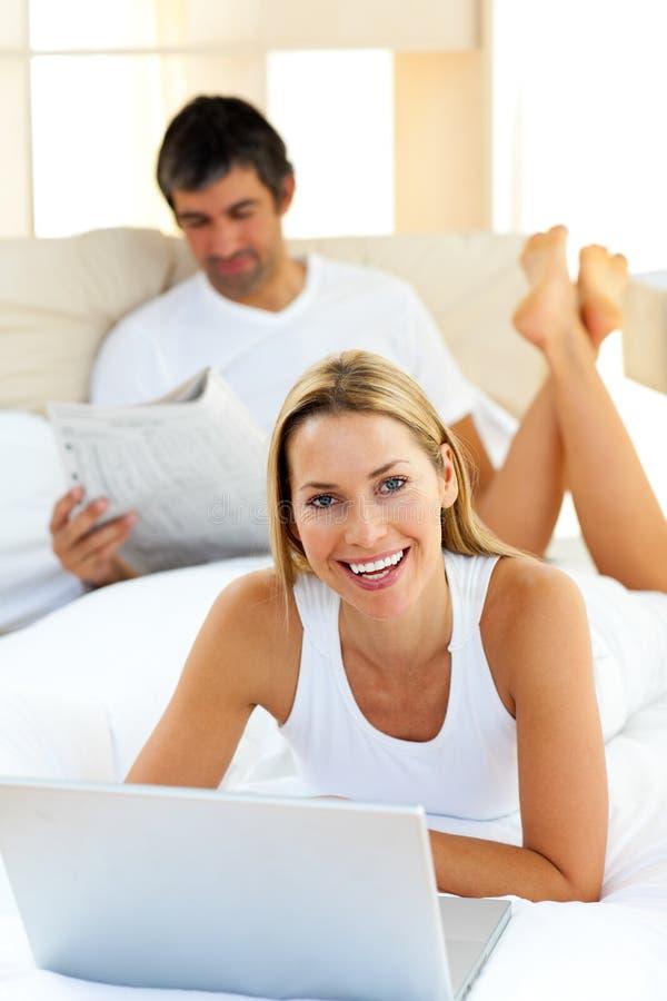 Download Mulher Bonita Que Usa Um Portátil Que Encontra-se Na Cama Imagem de Stock - Imagem de caderno, macho: 12811661