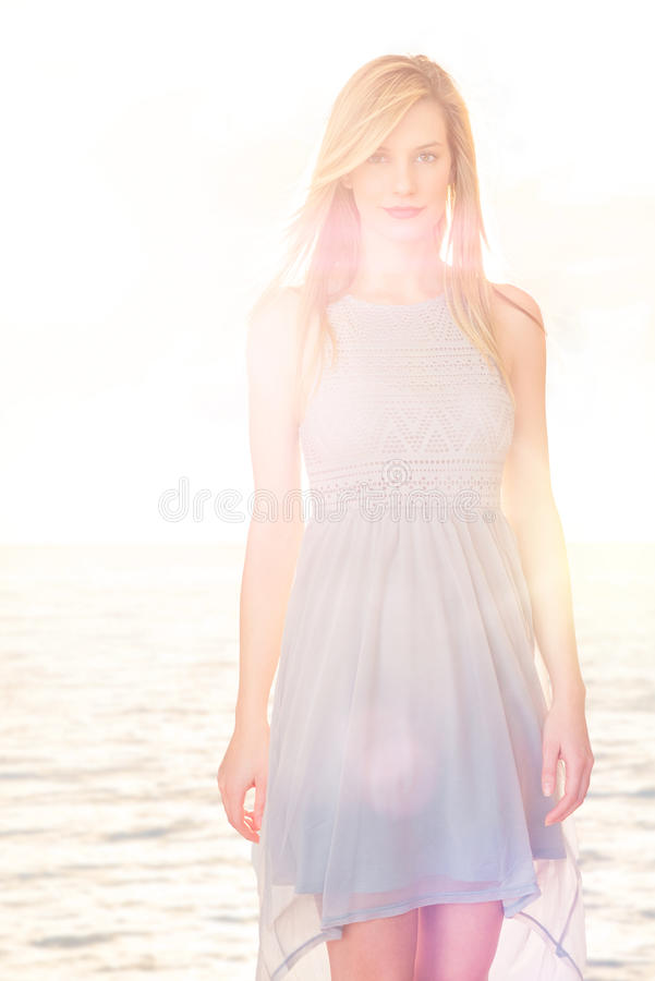 Mulher bonita que veste o vestido ocasional que está contra o mar no CCB imagens de stock