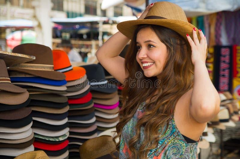 Mulher bonita que veste um chapéu de Panamá feito a mão no mercado do ofício em Otavalo, Equador, fundo colorido das telas foto de stock royalty free