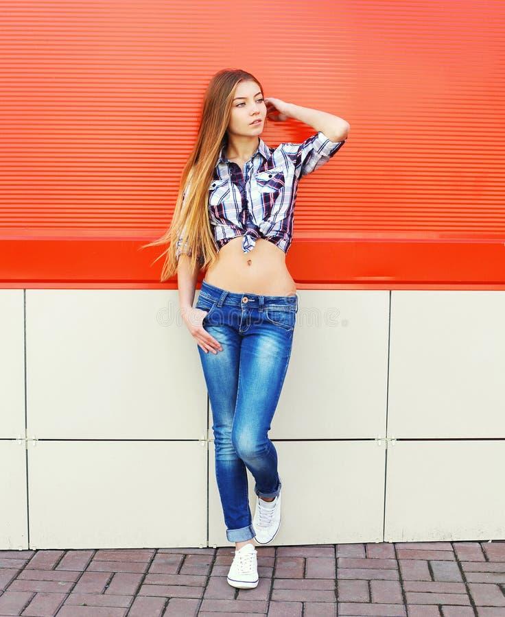 Download Mulher Bonita Que Veste Um Levantamento Quadriculado Da Camisa E Das Calças De Brim Foto de Stock - Imagem de longo, menina: 65577214