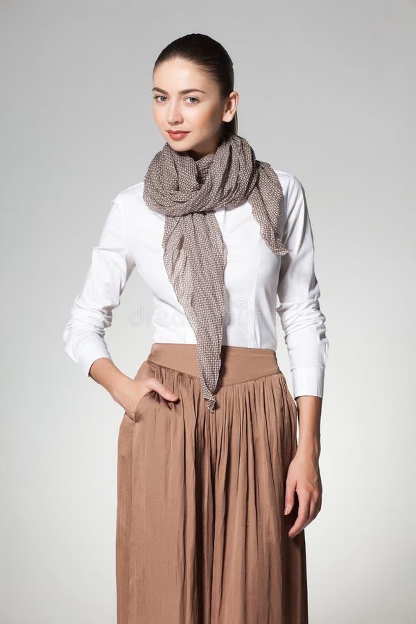 Mulher bonita que veste um scarve no fundo cinzento foto de stock royalty free