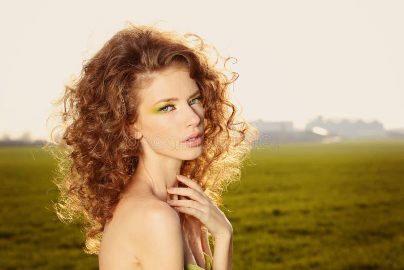 Mulher bonita que veste um vestido verde e que levanta nos campos fotografia de stock