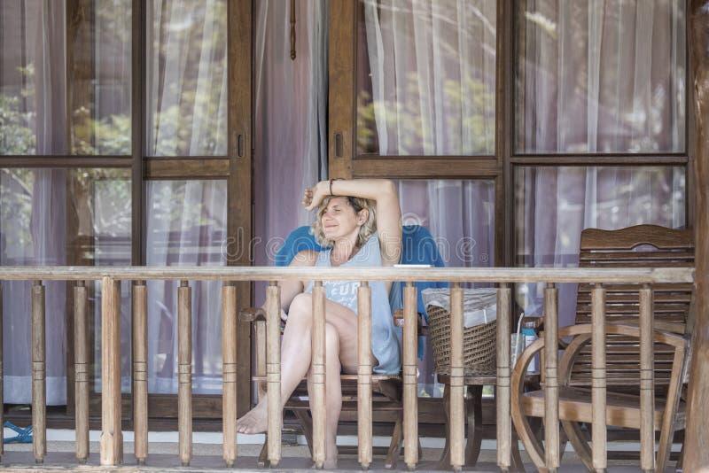 A mulher bonita relaxa no balcão do hotel imagem de stock