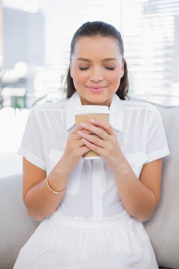 Mulher bonita relaxado que come o café que senta-se no sofá confortável fotografia de stock