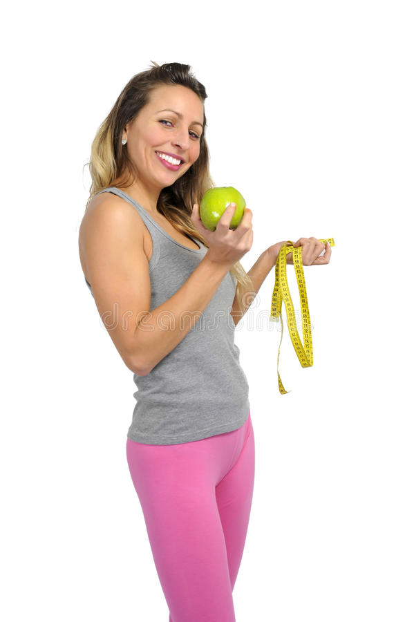 Mulher bonita 'sexy' que guarda o fruto verde da maçã e a medida da fita na dieta da nutrição e no conceito saudáveis da aptidão imagens de stock