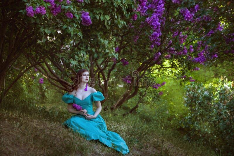 Mulher bonita sob um arbusto do lilás fotografia de stock royalty free