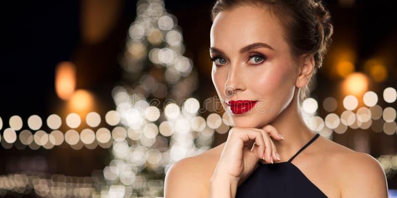 Mulher bonita sobre luzes da árvore de Natal fotografia de stock royalty free