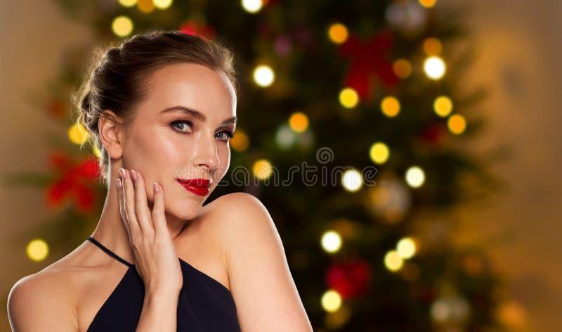 Mulher bonita sobre luzes da árvore de Natal fotos de stock royalty free