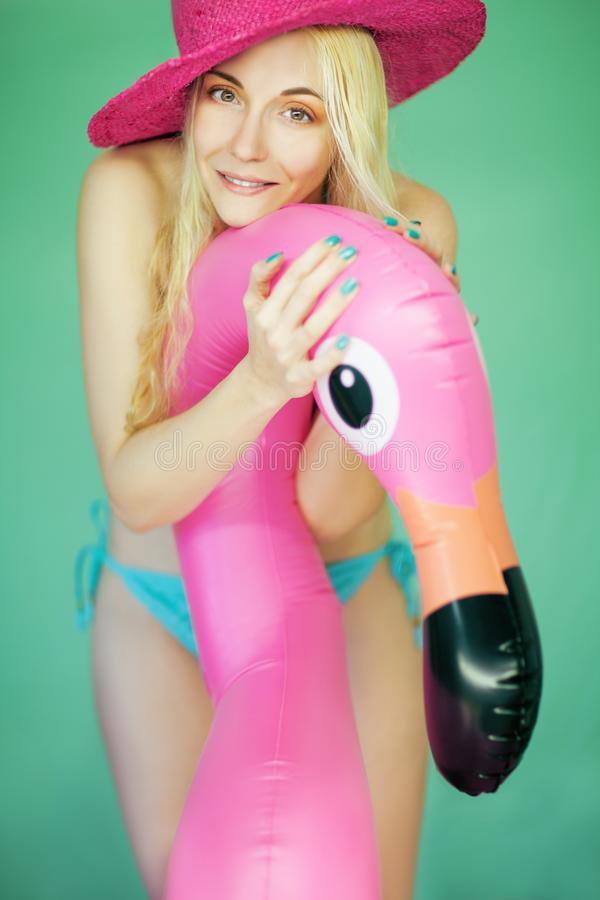 Mulher bonita summerly no humor da praia com chapéu, o biquini e o flamingo cor-de-rosa imagem de stock royalty free
