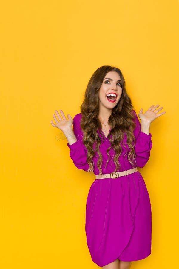 A mulher bonita surpreendida e feliz no vestido roxo está olhando afastado e gritaria fotografia de stock