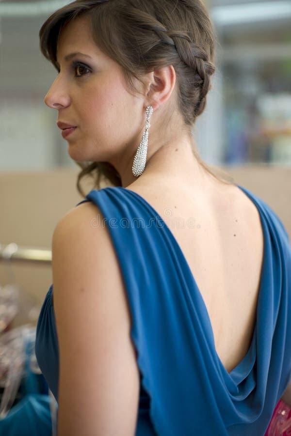 A mulher bonita tenta sobre um vestido fotografia de stock royalty free