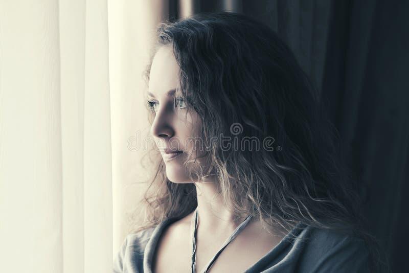 Mulher bonita triste que olha para fora a janela imagens de stock royalty free