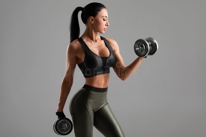 Mulher bonitinha fazendo exercício para bíceps em fundo cinza Mulher muscular se exercitando com estômagos imagens de stock