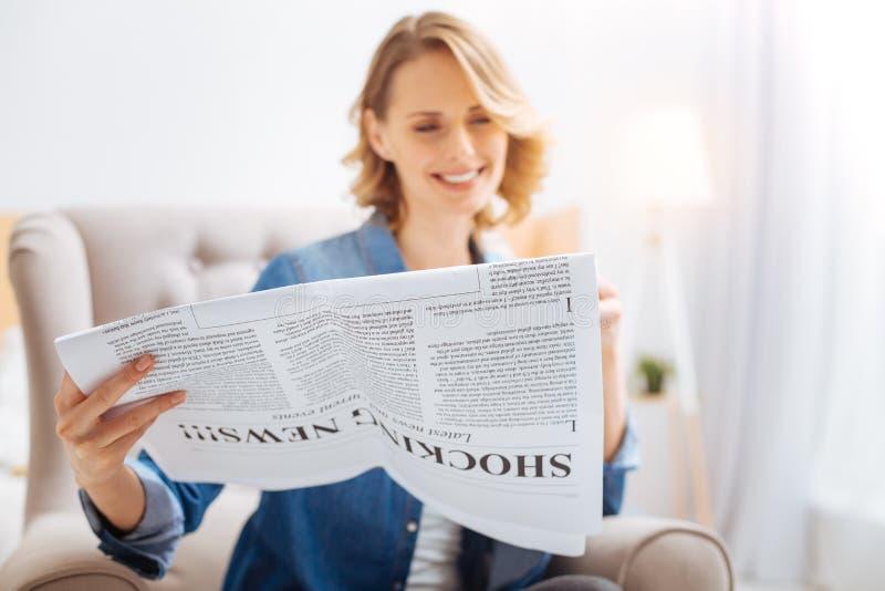 Mulher bonito agradável que sorri ao ler a notícia engraçada em um jornal local foto de stock royalty free