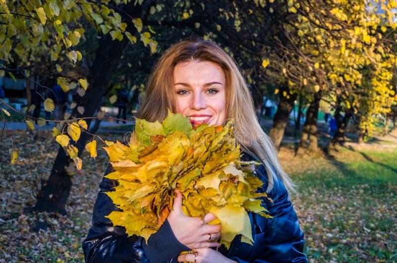 A mulher bonito alegre nova da menina que joga com amarelo caído do outono sae no parque perto da árvore, rindo e sorrindo imagens de stock