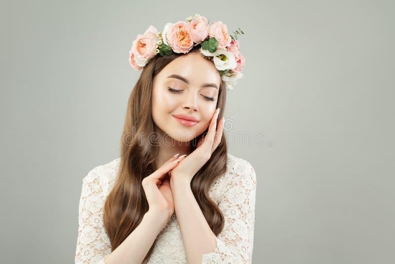 Mulher bonito com a pele clara, cabelo brilhante longo e flores relaxando fotos de stock royalty free