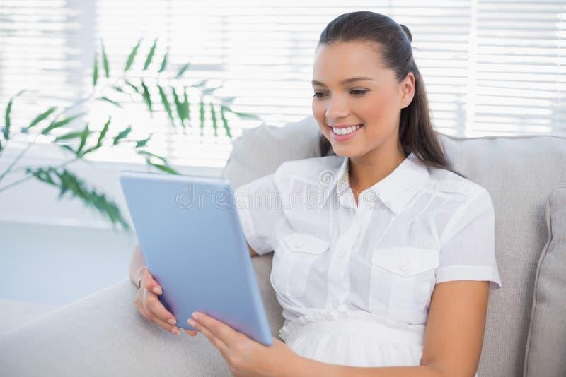 Mulher bonito de sorriso que usa a tabuleta que senta-se no sofá confortável imagens de stock
