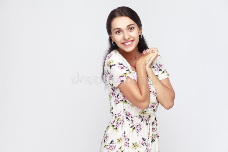 A mulher bonito e da felicidade nas flores veste-se, olhando a câmera e imagem de stock royalty free