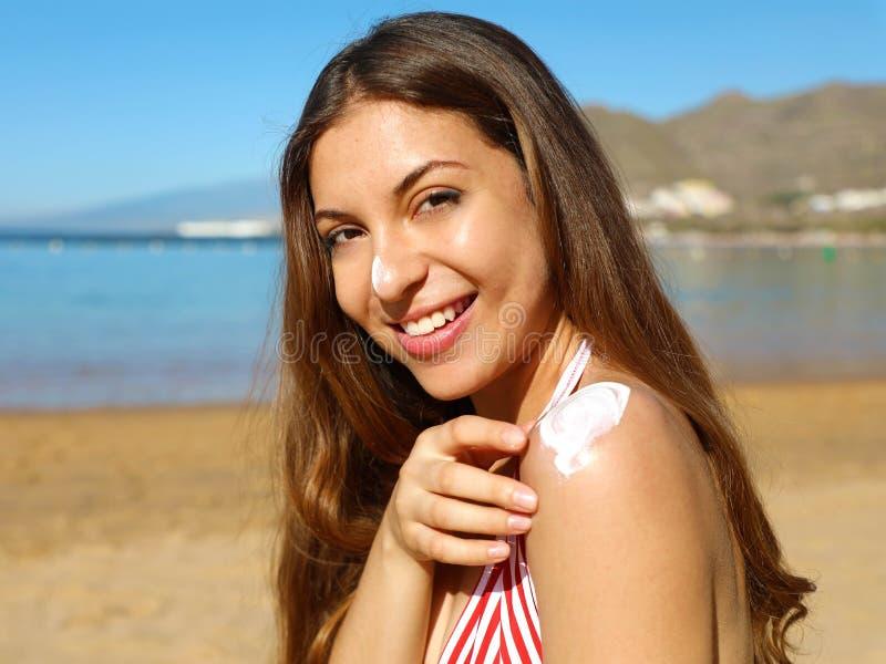 Mulher bonito feliz bonita que aplica o creme do bronzeado a seu nariz e o ombro com fundo da praia foto de stock