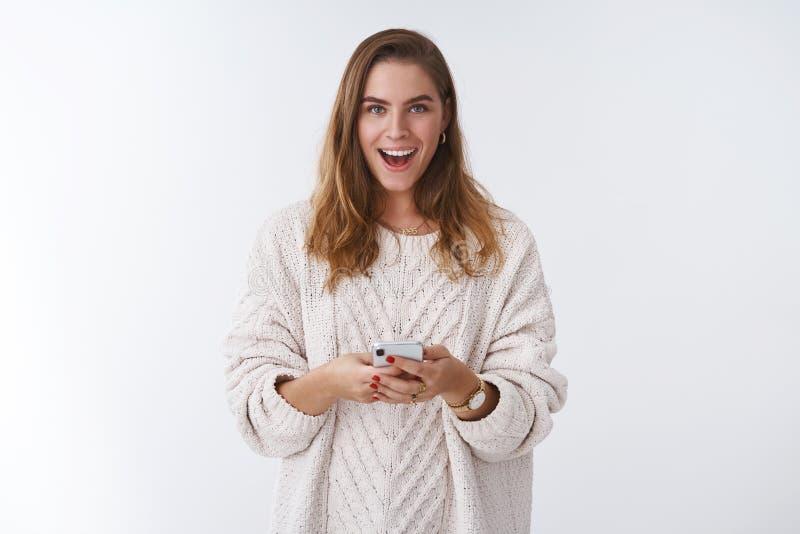 Mulher bonito intrigada Excited que recebe o smartphone guardando misterioso de sorriso satisfeito, mensagem da mensagem curiosa fotografia de stock royalty free