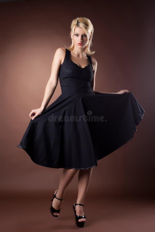 Mulher bonito na dança preta do estilo do pinup na obscuridade imagens de stock