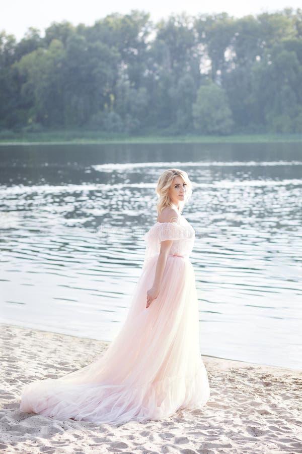 Mulher bonito na posição do vestido do verão na praia que olha o por do sol Estilo boêmio da roupa Menina bonita que anda no para foto de stock