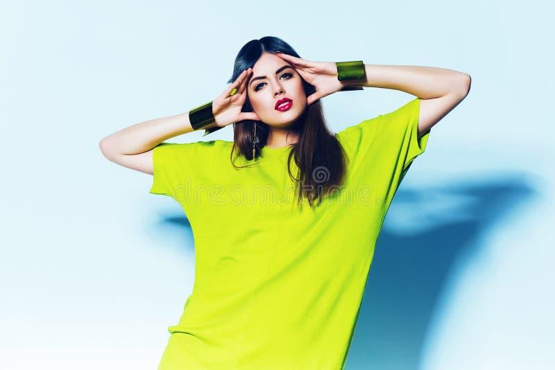 Mulher bonito no vestido verde de néon no fundo azul fotos de stock