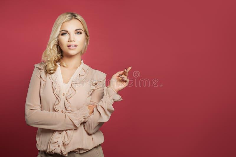 Mulher bonito nova que aponta acima contra o fundo cor-de-rosa da parede Menina ocasional do estudante que aponta o dedo fotos de stock royalty free