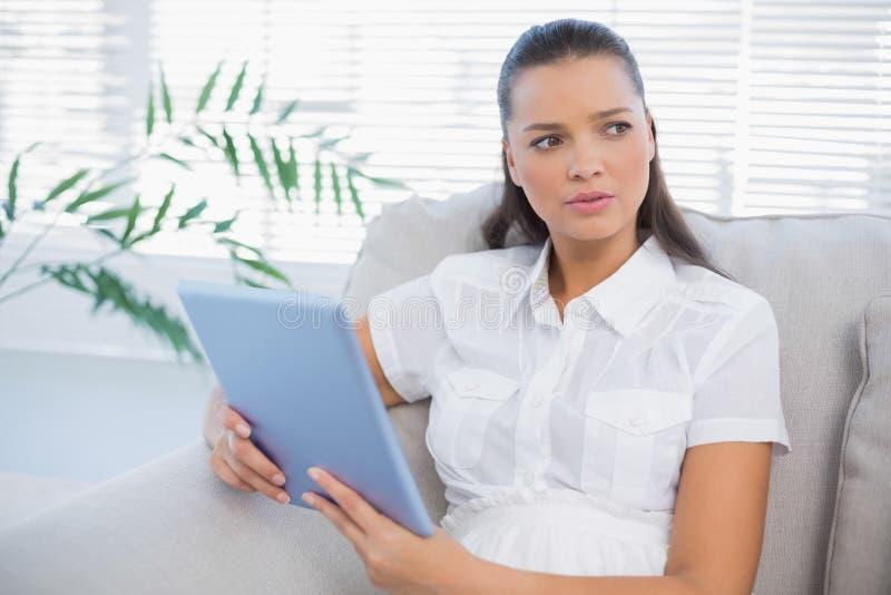 Mulher bonito pensativa que usa a tabuleta que senta-se no sofá confortável foto de stock