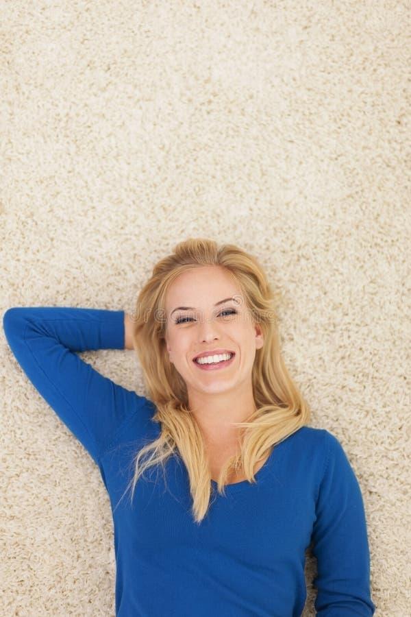 Mulher bonito que relaxa no tapete foto de stock